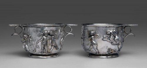 Esses taças de prata representam metal romano da mais alta qualidade no século 1 d.C. Eles foram indubitavelmente produzidos por uma das principais oficinas romanas que abasteciam a família imperial, bem como indivíduos particulares ricos e cultos. Elas são decoradas em alto relevo com figuras de cupidos dançando e tocando instrumentos, e podem estar associados a festividades dionisíacas e, portanto, eram adequados em festas de bebida. MET. N° 1994.43.1, .2