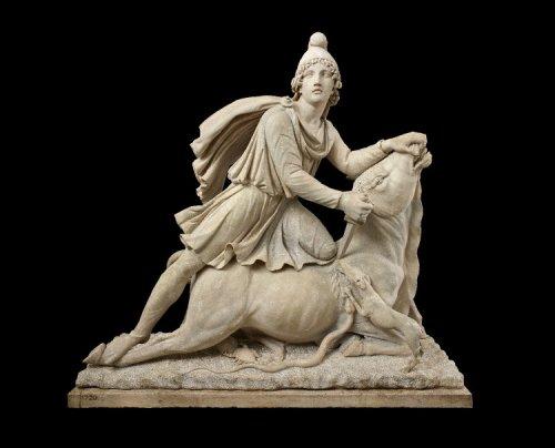 Estátua de mármore de Mitra sacrificando um touro. Mitra é mostrado em roupas orientais, incluindo calça e chapéu frígio. Um cachorro e uma cobra aparecem tentando lamber o sangue e um escorpião está atacando as genitálias do touro. A prática de sacríficio de touros era comum no culto a Mitra. Século 2 d.C. Museu Britânico. N° 1825,0613.1