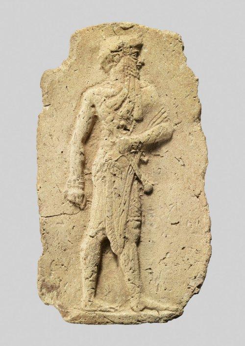 Placa com imagem de rei ou deus carregando um bastão